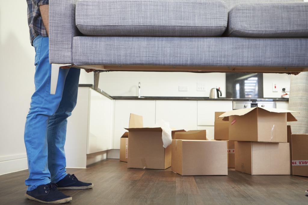Man Carrying Sofa As He Moves Into New Home
